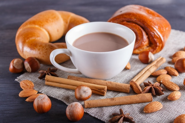 A cup of hot chocolate with nuts, buns and spices on black wooden background.