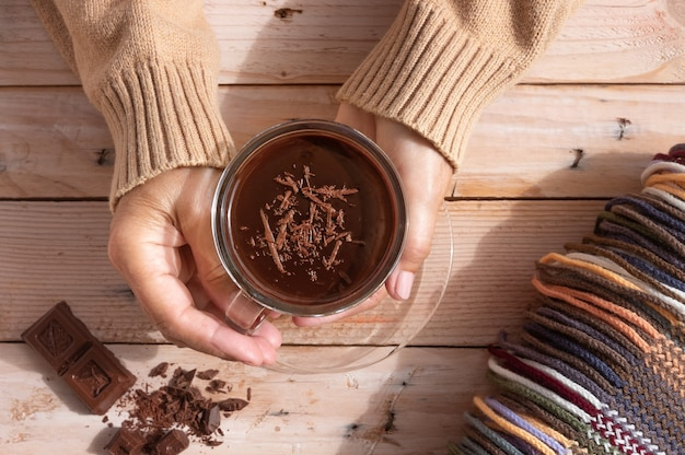 Cup of hot chocolate in woman's hands and pieces of chocolat on wooden rustic table