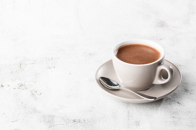 Cup of hot cocoa or hot chocolate or americano in white cup isolated on bright marble background. overhead view, copy space. advertising for cafe menu. coffee shop menu. vertical photo. traditional