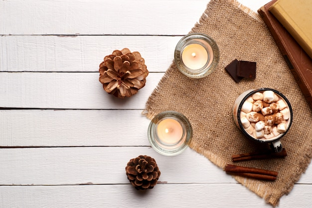 Cup of hot cocoa or hot chocolate with marshmallows and cinnamon sticks on wooden background with burning candles. rustic. winter mood. flay lay.