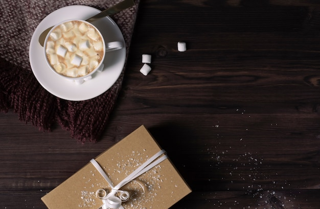 A cup of hot cocoa and marshmallows, a knitted scarf and a gift box on a dark wooden background.