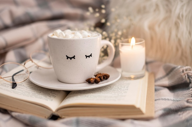 Cup of hot cocoa with marshmallows on book with candle