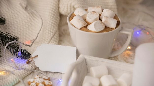 Cup of hot cocoa with marshmallows and sweater with tag