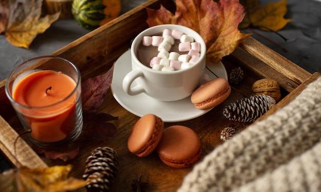 A cup of hot cocoa with marshmallows on a wooden tray with macaroons pine cones and fallen leaves
