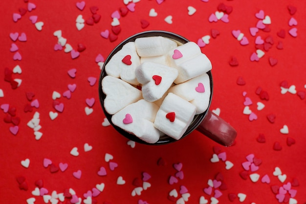 Cup of hot coffe with heart shaped marshmallows and confetties on red