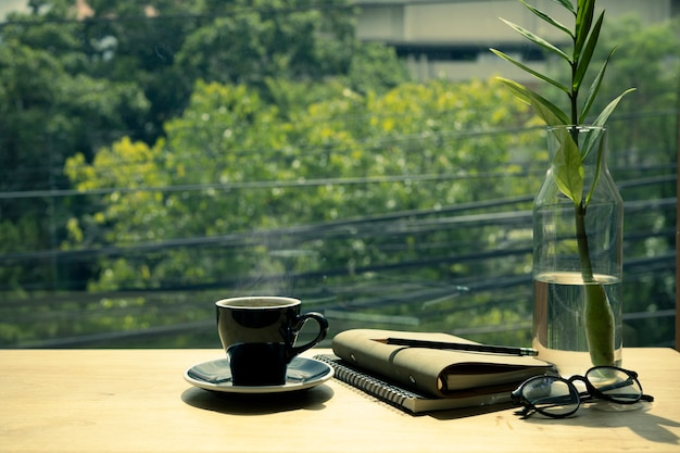 Cup of hot coffee, book, eyeglasses and plant on wooden table.