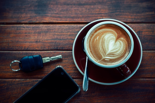 Cup of hot coffee,books,smart phone and keys on the wood plate