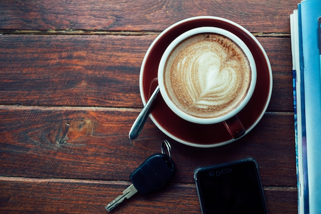 Cup of hot coffee, books, smart phone and keys on the wooden plate