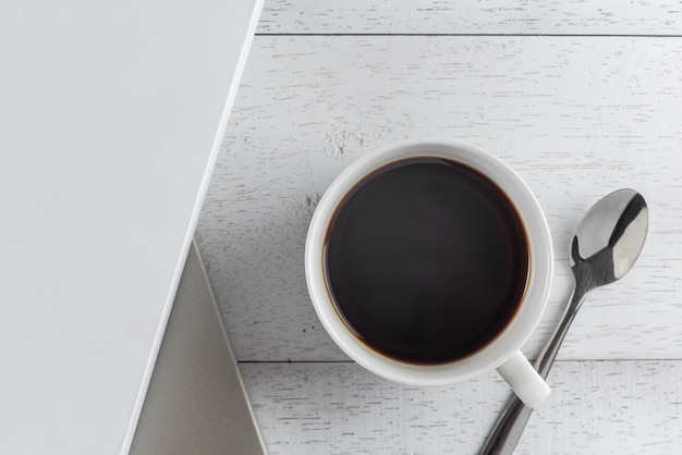 A cup of hot coffee and books on wooden table, top view