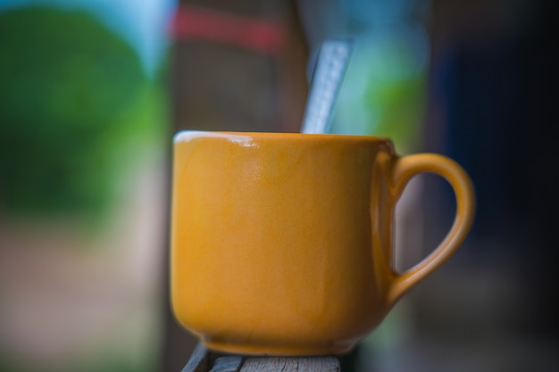 The cup of hot coffee in the cafe garden with blur bokeh background and space for putting text