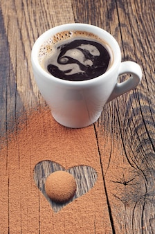 Cup of hot coffee, candy and chocolate in the shape of hearts