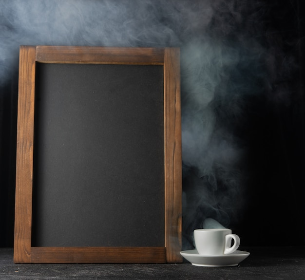 A cup of hot coffee and a chalk board