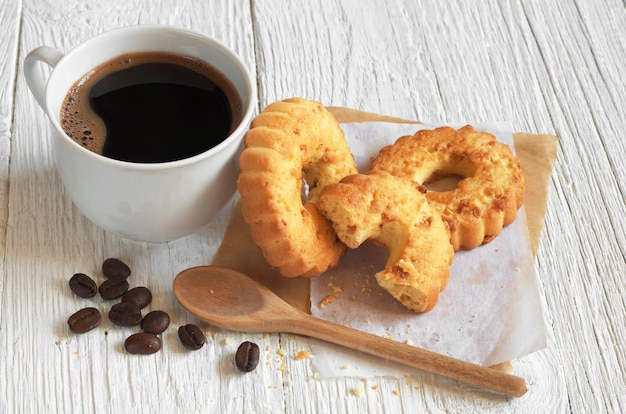 Cup of hot coffee and cookies rings with nuts