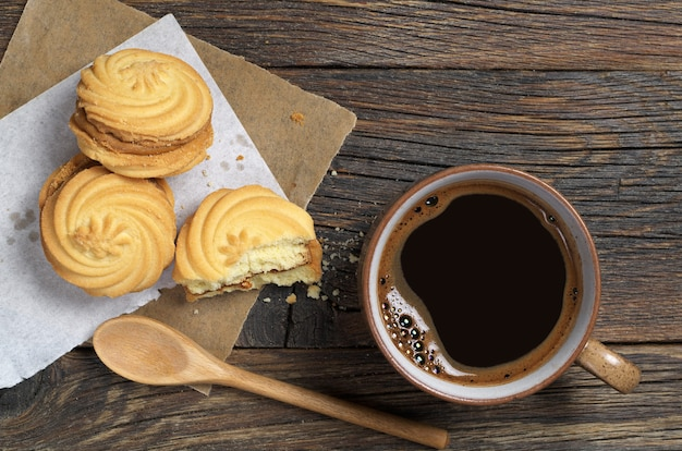 Cup of hot coffee and cookies with caramelized milk filling for breakfast on dark wooden table, top view