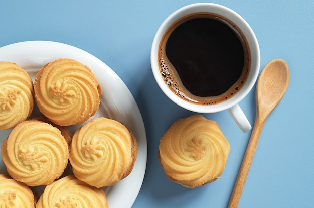 Cup of hot coffee and cookies with condensed milk for breakfast on blue table, top view