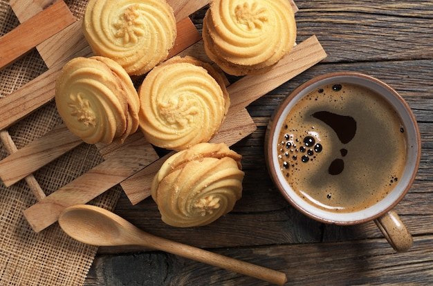 Cup of hot coffee and cookies with condensed milk for breakfast on rustic wooden background, top view