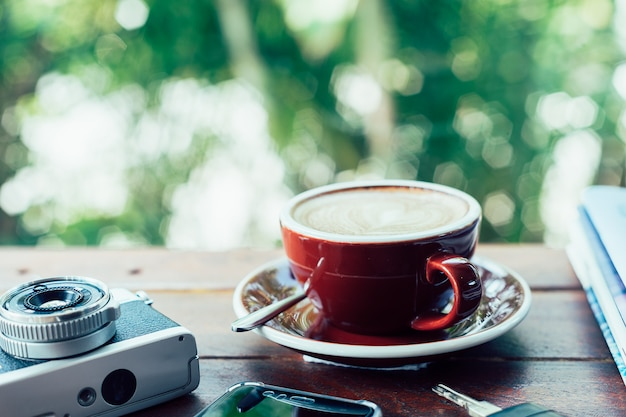 Cup of hot coffee,film camera,books,smart phone and keys on the wood plate