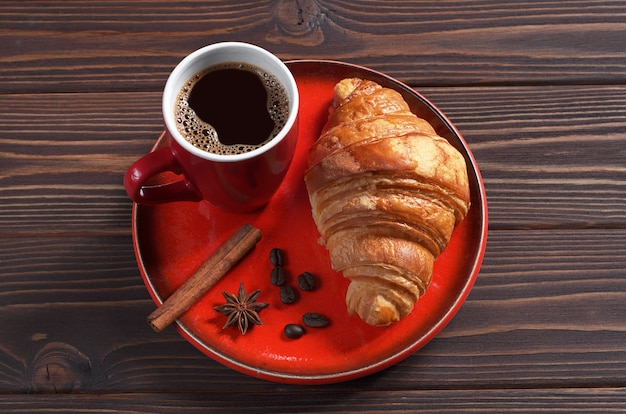 Cup of hot coffee and fresh croissant in red tableware on dark wooden table