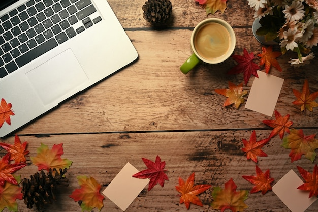 Cup of hot coffee, laptop computer and autumn maple leaves on wooden background.