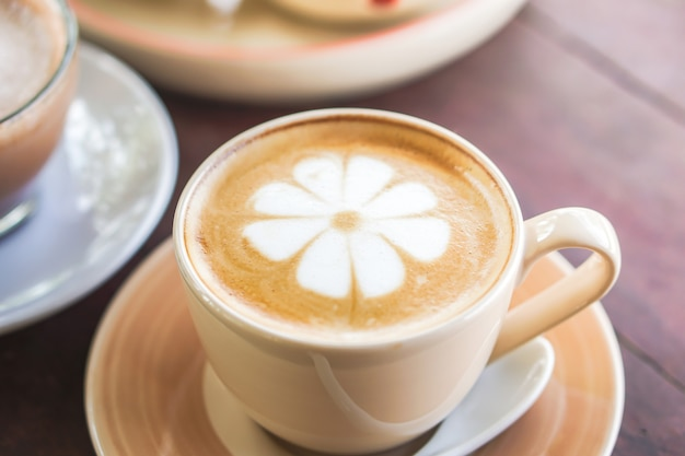 Cup of hot coffee latte art on wooden table