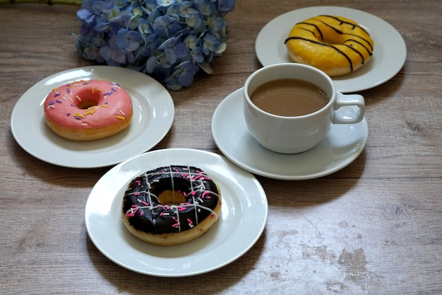 A cup of hot coffee and a mix of multicolored sweet donuts