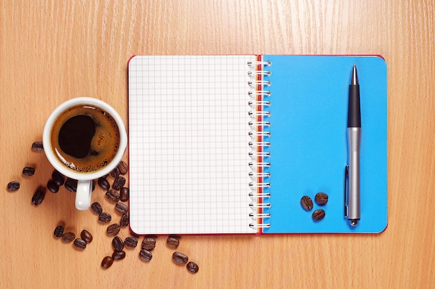 Cup of hot coffee, opened notebook and pen on wooden table, top view