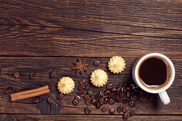 Cup of hot coffee and small cookies on dark wooden table, top view