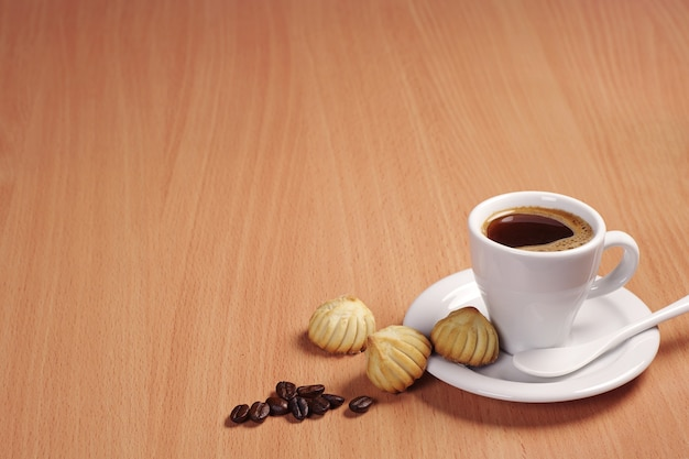 Cup of hot coffee and small cookies on wooden table