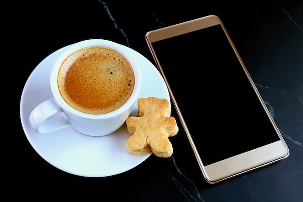Cup of hot coffee and teddy bear shaped cookie with blank screen mobile phone on black table