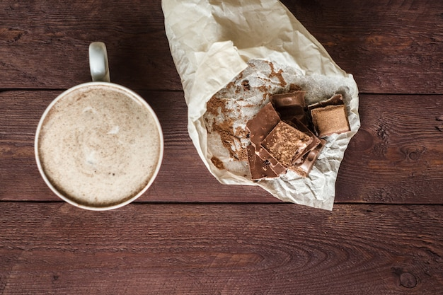 A cup of hot coffee with chocolate slices on a wooden table