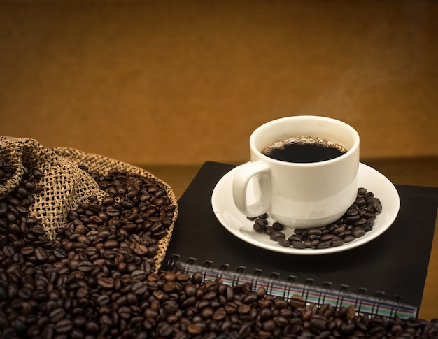 A cup of hot coffee with coffee beans