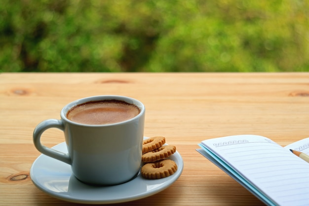 A cup of hot coffee with cookies and lined note papers on the wooden table of outdoor seating