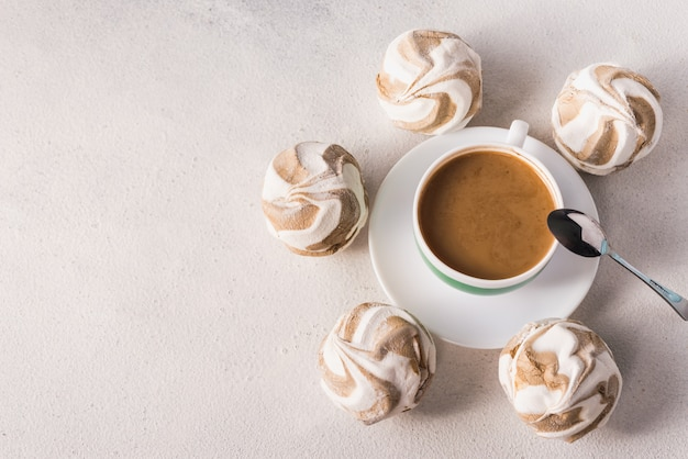 Cup of hot coffee with milk and aromatic spices and sweet marshmallows and cookies for a good morning top view