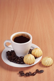 Cup of hot coffee with small cookies on desk