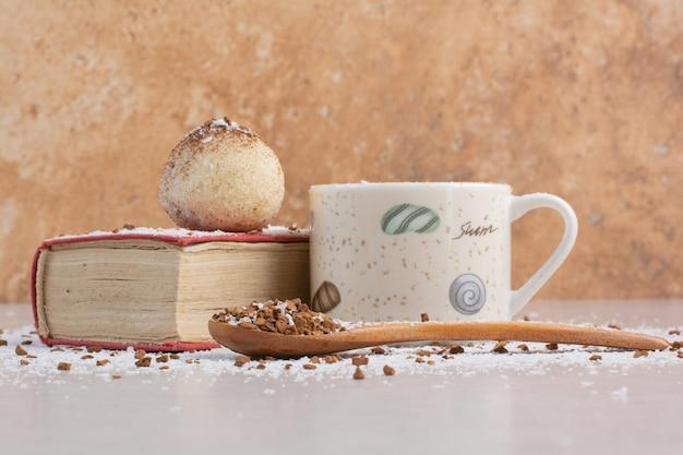 Una tazza di caffè caldo con un cucchiaio e un su8gar sulla superficie bianca