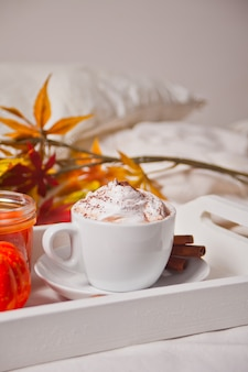 Cup of hot creamy cocoa with froth on the white tray with autumn leaves and pumpkins on the background