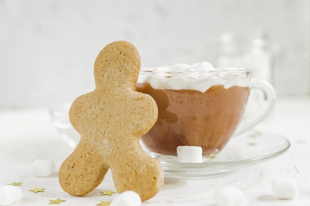 Cup of hot delicious cocoa drink with marshmallows and ginger man.