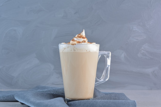 Una tazza di caffè delizioso caldo decorato con cacao su panno blu.