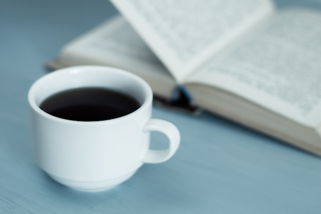 A cup of hot drink, coffee and an open book.