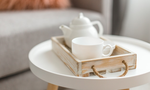 Cup of hot drink and teapot on a serving tray on table