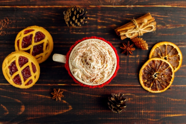 A cup of hot drink with whipped cream and powder, in a knitted cover and homemade cookies, cezve and spices, lie on a wooden table.