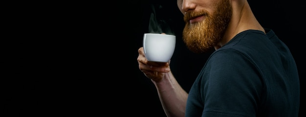 Cup of hot espresso coffee in the hand of a young bearded guy. close-up studio shot on black background. copy free space on left.