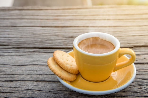 Cup of hot espresso coffee mugs placed with cookies on a wooden floor with morning fog and moutains with sunlight