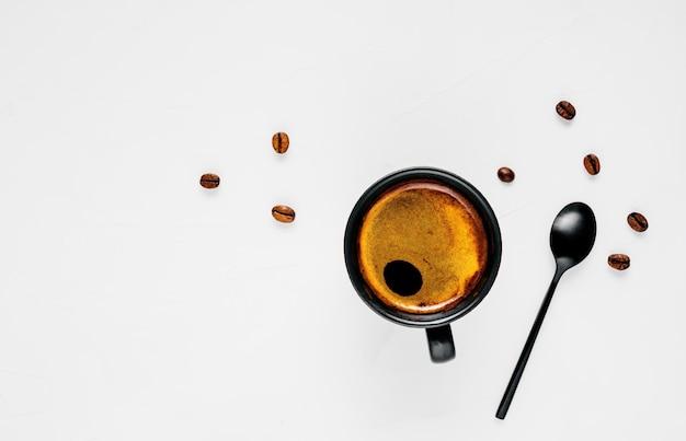 Tazza di caffè espresso caldo con schiuma, situata su un'ampia superficie bianca