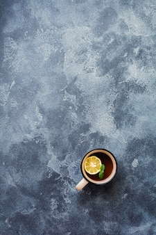 Cup of hot ginger tea with lemon and honey on dark gray surface