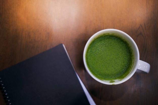 Cup of hot green tea latte and notebook on the table in house or cafe