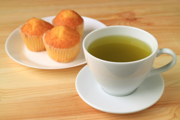 Cup of hot green tea with blurry madeleine cupcakes in background served on wooden table