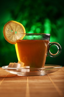 Cup of hot green tea with sugar and lemon