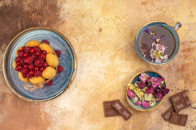 A cup of hot herbal tea soft cake with fruits flowers chocolate bars on mixed color table