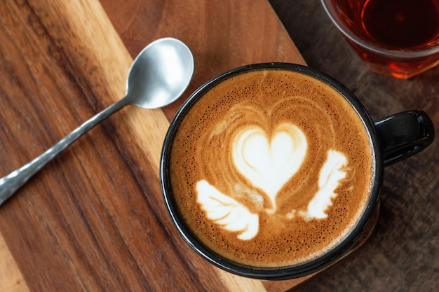 A cup of hot latte art coffee on wood background